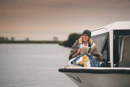 A lady enjoying a Broom boating holiday