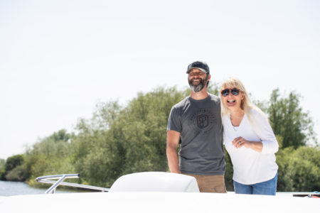 Man and a woman on a Norfolk Broads hire boat